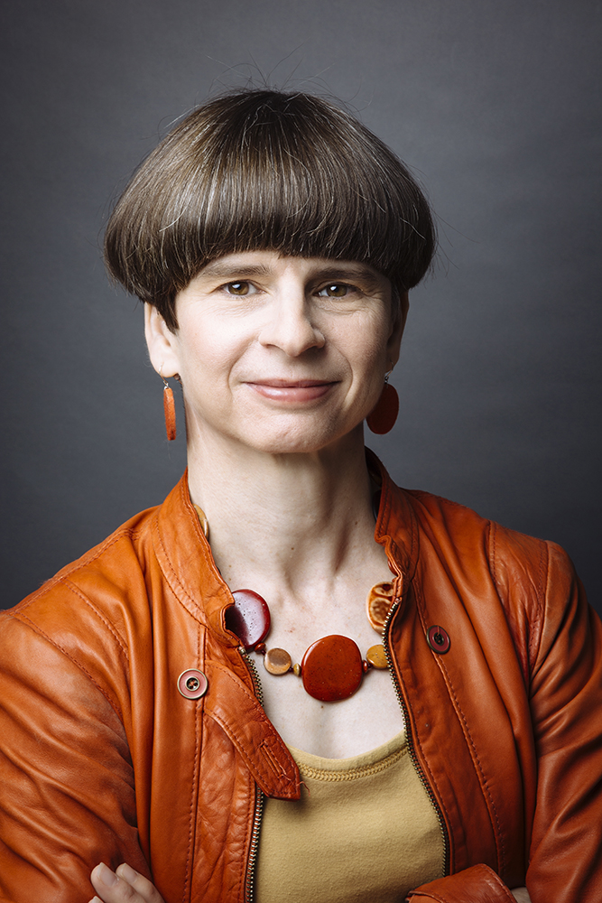 Portrait of Elizabeth Merritt, facing camera with arms crossed, in orange leather jacket and yellow blouse with orange disc-shaped earrings and pendant necklace, against a mottled gray background.